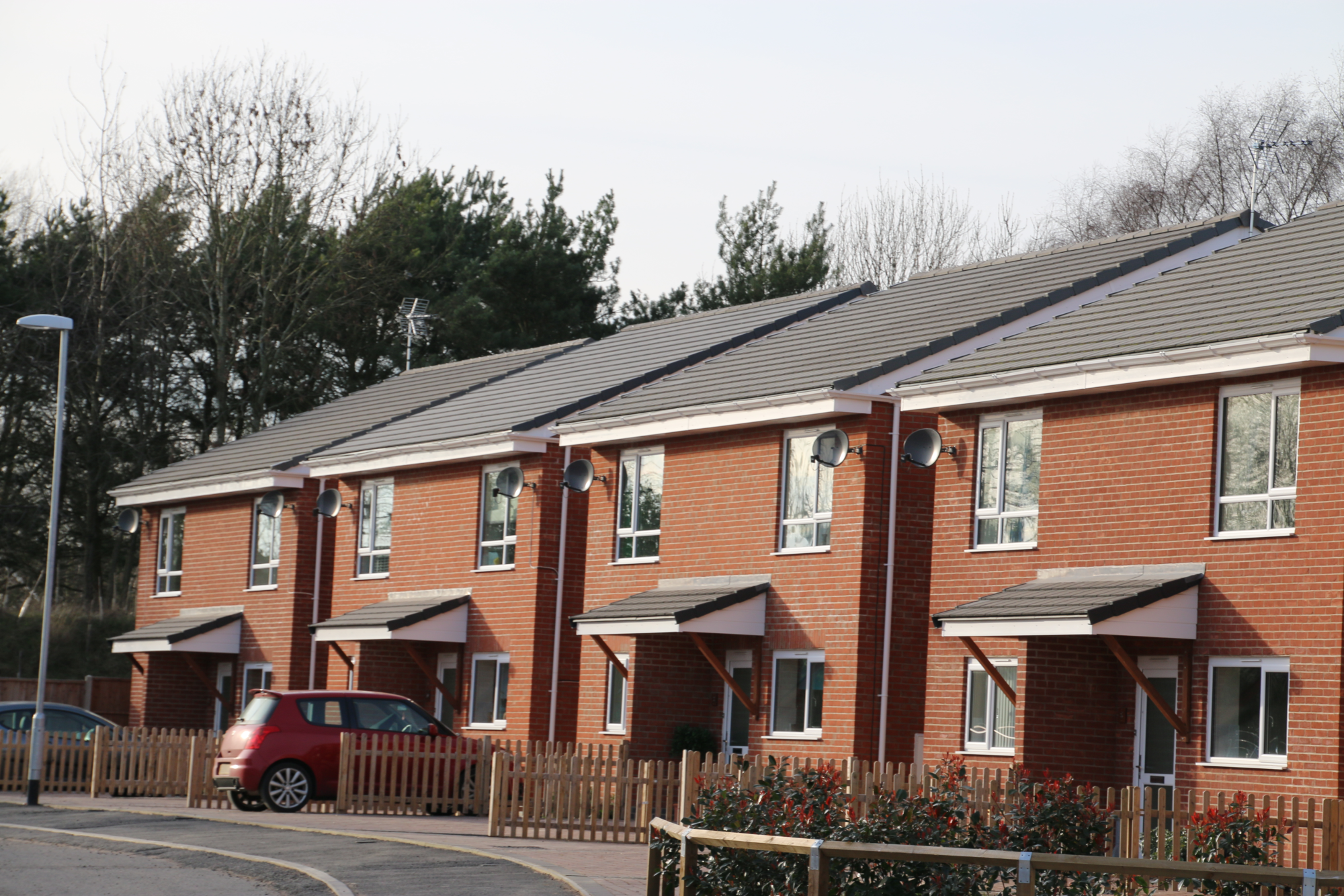 A line of new build houses with pitched tiled roofs